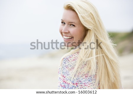 Woman standing at beach smiling - stock photo
