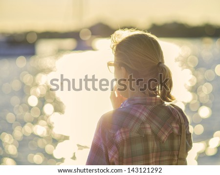 Woman standing at the edge of a bay staring out at the water while thinking or relaxing. - stock photo