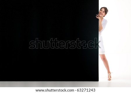 Woman standing behind black empty billboard on white backgrounds. - stock photo