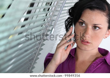 Woman standing by a window and talking on her mobile phone - stock photo