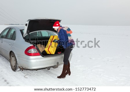 Woman standing by the open trunk and invites gift - stock photo