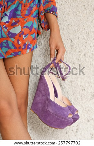 woman standing holding platform wedges shoes with open open toe - stock photo