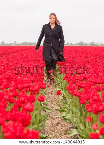 Woman standing in a field of tulips, selective focus