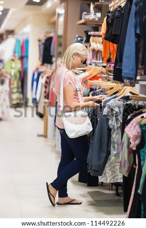 Woman standing in a shop looking at clothes - stock photo