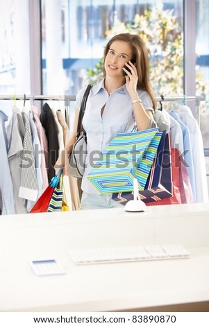 Woman standing in clothes shop, holding shopping bags, speaking on mobile phone, smiling.? - stock photo