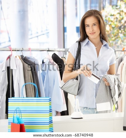Woman standing in clothes shop, paying with credit card, smiling at camera.?
