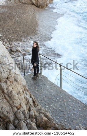 Woman standing in front of beach and wild sea