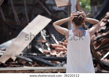 woman standing in front of burned out house and holding her head with both hands - stock photo