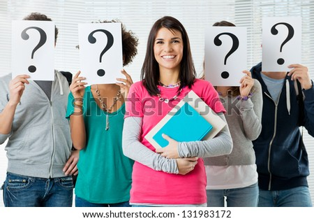 Woman Standing In Front Of Friends Holding Paper With Question Mark Signs - stock photo