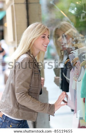 Woman standing in front of shopping windows - stock photo