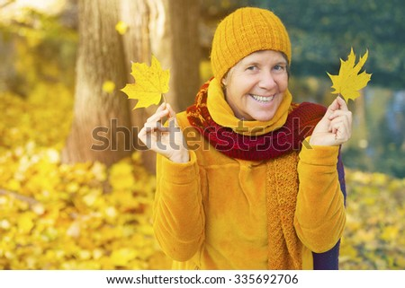 woman standing in front of trees in the fall and holding leaves in her hands