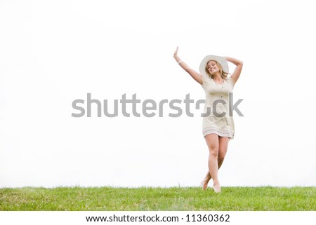 Woman standing in grass with her arms up in the sky - stock photo