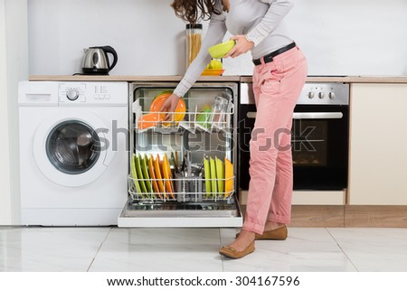 Woman Standing In Kitchen Removing Bowls From Dishwasher - stock photo