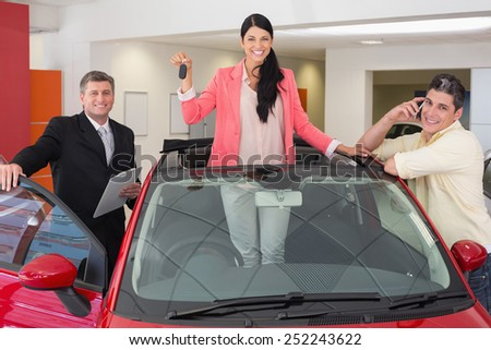 Woman standing in red cabriolet while holding her car key at new car showroom - stock photo