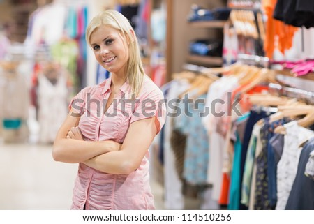Woman standing in shop smiling with arms crossed - stock photo