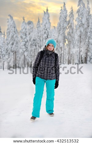 Woman Standing In Snow Wearing Warm Clothes On Ski Holiday In mountain forest