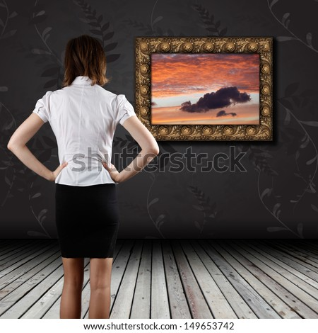 Woman standing in the gallery and watching art - stock photo