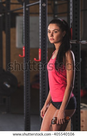 woman standing in the gym and holding rope - stock photo