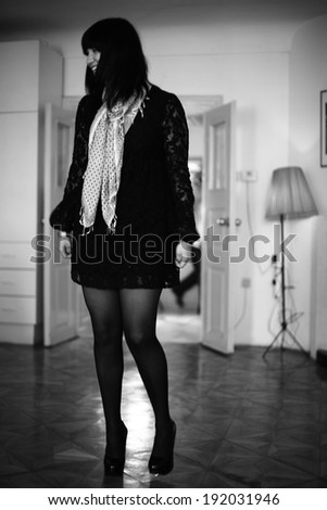 woman standing  in the middle of the room , black haired woman posing on white background - stock photo