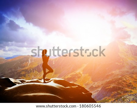 Woman standing in tree yoga position, meditating on rock in mountains at sunset. Zen, meditation, peace - stock photo
