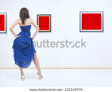 Woman standing inside a gallery in front of three picture frames. Images are fill with red color useful for copy space. NOTE:This image is composite of more photos. - stock photo