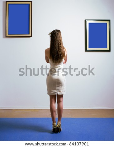Woman standing inside a gallery infront of two picture frames. Images are fill with blue color - stock photo