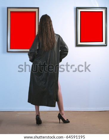 Woman standing inside a gallery infront of two red picture. - stock photo