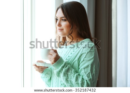 Woman standing near window in the room, close up - stock photo