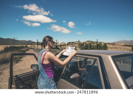 Woman standing next to old car reading a map. Swartberg. Western Cape. South Africa. - stock photo