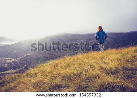 Woman standing on a mountain top - stock photo