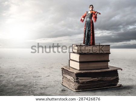 Woman standing on a pile of books - stock photo