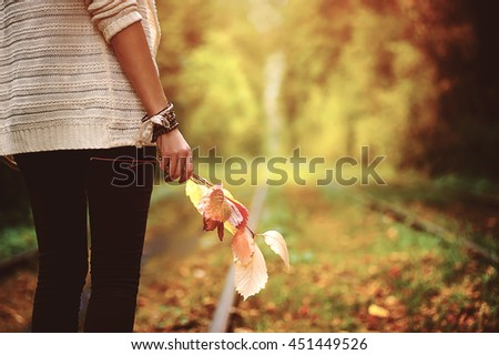 woman standing on alley and holding colorful autumn leaves on hands. natural autumn background - stock photo