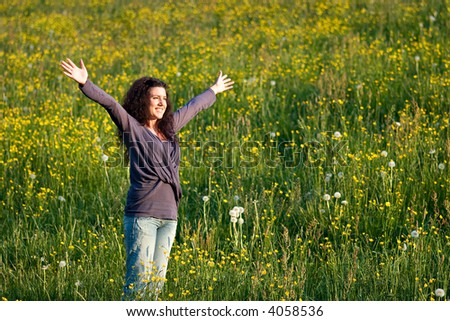 Woman standing on flowered field, looking happy. - stock photo