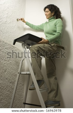 Woman standing on ladder scrapes wall while holding paint tray and roller. Vertically framed photo. - stock photo