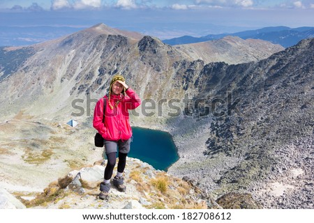 Woman standing on mountain edge above lake in Rila national park of Bulgaria.