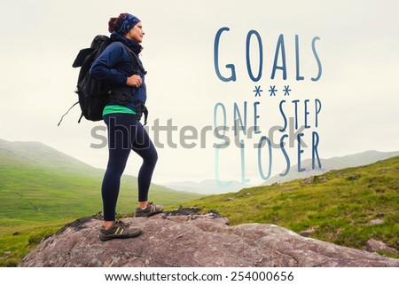 Woman standing on rock admiring the view against goals one step closer - stock photo