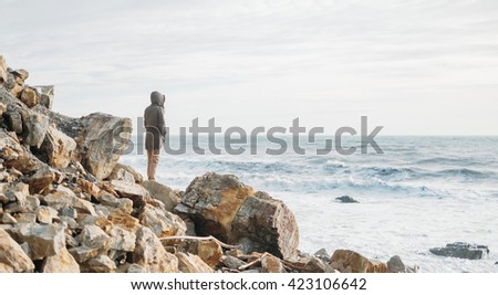 Woman standing on stone coast and enjoying view of sea