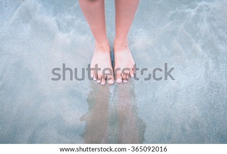 Woman standing on the beach with wave sea, Top view. - stock photo
