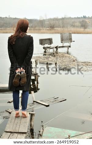Woman standing on the edge of a broken bridge over water - stock photo