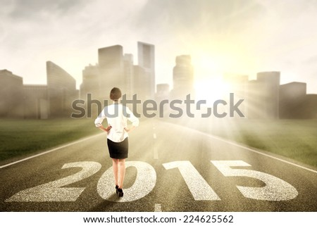 Woman standing on the road looking a chance in the future 2015 - stock photo
