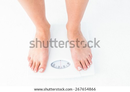 Woman standing on the scales on white background