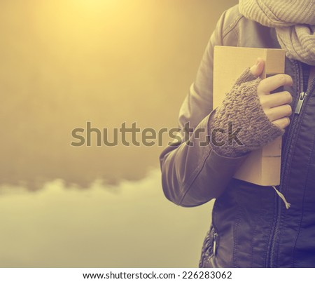 Woman standing with a book at the lake in sunset - stock photo