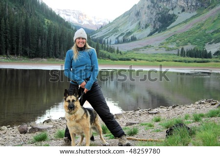 Woman standing with dog at lake