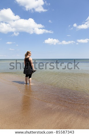 Woman standing with feet in the water watching towards the horizon. Sky is blue with tiny clouds - stock photo