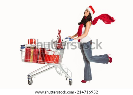 Woman standing with shopping trolley on white background - stock photo