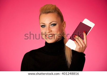 Woman standing with travell documents excited to go on vacations. - stock photo