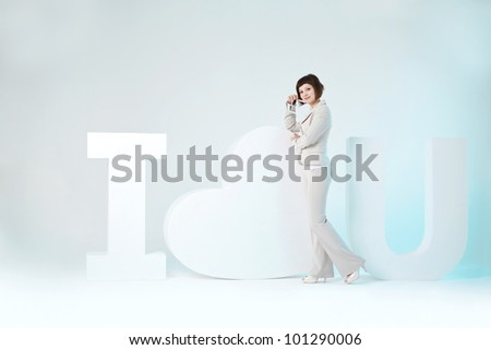 Woman stands near a big sign I love you - stock photo