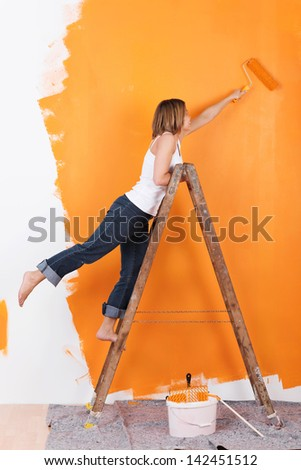 Woman stands on a ladder to paint her walls orange - stock photo