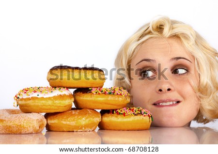Woman stares wantingly at a donut - stock photo