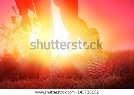 woman starting her race at a sunrise sprint.  - stock photo